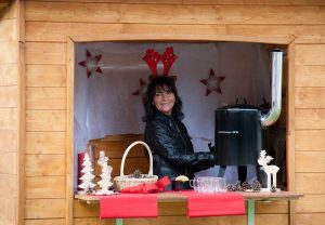 A member of staff serves hot punch and mulled wine, wearing a festive pair of felt antlers