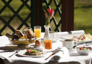 The breakfast table is decked out in style with an ornamental red tulip. A tasteful spread to tempt the taste buds, including coffee, tea, juice, ham, cheese and salad.