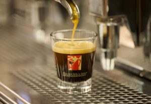 Coffee flowing from the machine into an espresso glass – the crema is simply divine!