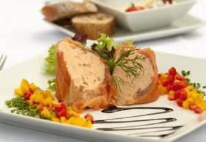 Two slices of salmon terrine, garnished with herbs, salad and diced peppers.