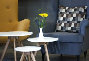 Yellow and grey stylish armchairs with cushions arranged around three small round tables are perfect for lounging comfortably in the lobby