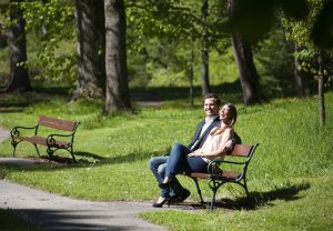 A couple relaxing and enjoying the sun on a bench in the hotel park