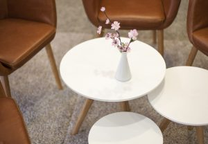 Image shows three round, white tables in the lobby. Brown leather-look armchairs are arranged around the tables. A small vase of flowers stands on one of the tables.