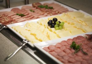The breakfast buffet includes a range of temptingly displayed sausage meat and cheese varieties, garnished with herbs and grapes.