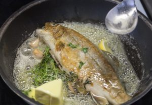 The trout sizzles in the pan with butter and fresh herbs