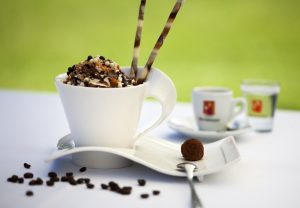 Hirschwang iced coffee is served in an elegant coffee cup, decorated with chocolate sprinkles and chocolate wafer sticks