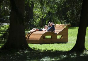 A couple relaxing on the wooden lounger in the middle of the park – it looks so cosy here in the sunshine!