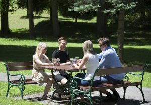 There are lots of places to chill out in the park on loungers or benches – here, four adults are playing a party game in the afternoon sun