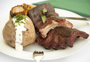 Crispy ribs with oven-baked potatoes and barbecued corn on the cob