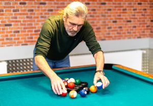 A man with billiard balls is getting the billiard table located next to the basement bar ready for a game