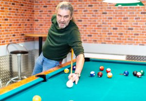 A billiards game is in full swing – this player is aiming to take a shot